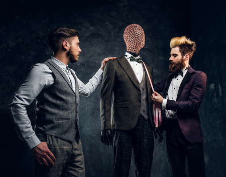 Two fashion designers working with custom made mens suit in a dark tailor studio