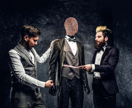 A fashion designer with a client checking custom made mens suit in a dark tailor studio