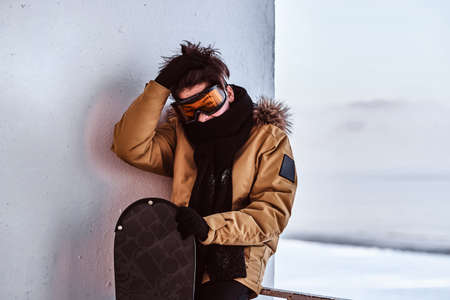 Outdoor activities during the winter holidays. A teenage snowboarder dressed in warm clothes and protective goggles sitting on railing near the snowy beach