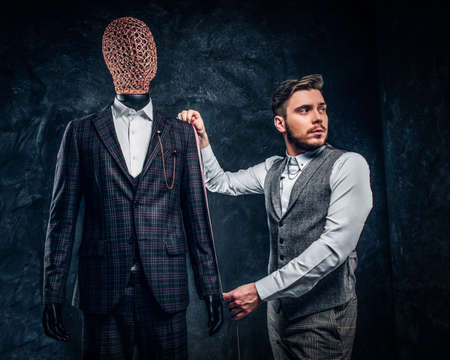 A young fashion designer with a measuring tape check the length of the sleeves of a custom made elegant mens suit in a dark tailor studio. Stock Photo