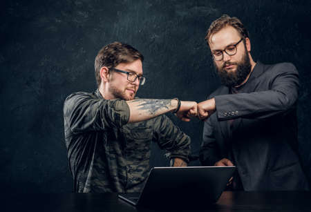Friendship, brofist, cooperation. Two programmers colleagues fist bumping after completion of the general project in the office against a dark wall Stock Photo