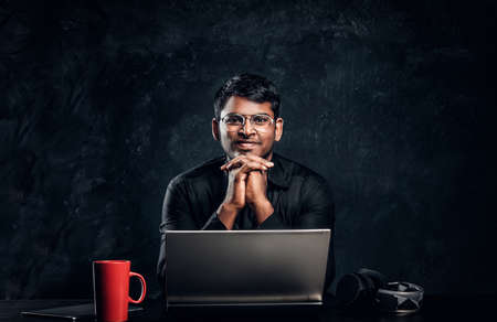 Smiling Indian student sitting at a desk with laptop, leaning chin on his hands and looking at a camera. Studio photo against a dark textured wall