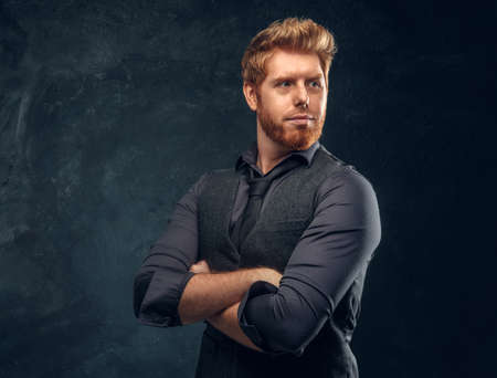 Handsome elegantly dressed redhead man posing with his arms crossed in studio against a dark textured wall