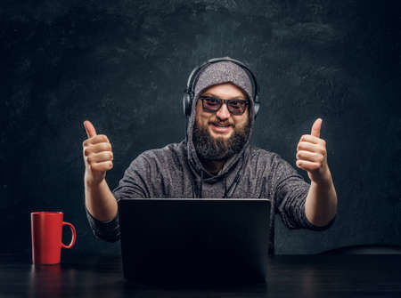 Satisfied hacker sits behind a laptop in a dark office Stock Photo