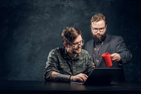 Serious bearded manager looks into the laptop together with smiling it expert on black background