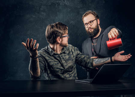 Dissatisfied customer pours coffee on the hackers loptop on a black background Stock fotó