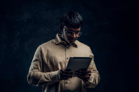 Indian male in eyewear and shirt using a tablet computer in studio against the background of the dark wall