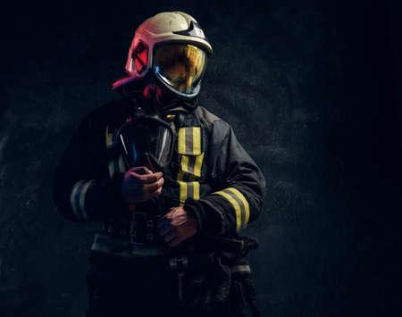 Manly firefighter in helmet looks sideways in studio on black background Stockfoto