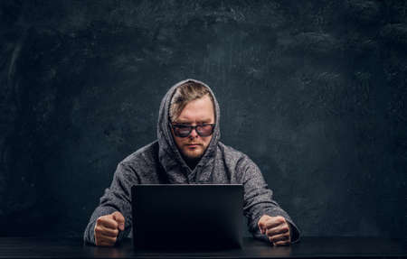 Disgruntled hacker in hoodie and sunglasses sits behind laptop in office against a dark wall