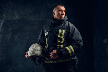 Brutal firefighter looks sideways and holds a helmet in his hand in the studio on a black background