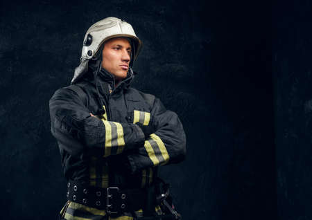 Portrait of a fireman in uniform and helmet stands with crossed hands, looking sideways with a confident look. Studio photo against a dark textured wall