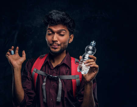 Handsome Indian hiker with backpack got a stirring sensation drank a sip of fresh water. Studio photo against a dark textured wall Imagens