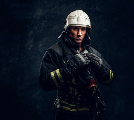 Firefighter in uniform and safety helmet posing in a dark studio, looking at the camera with a confident look.