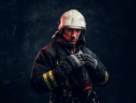 Manly firefighter in helmet looks into camera in studio on black background Stockfoto