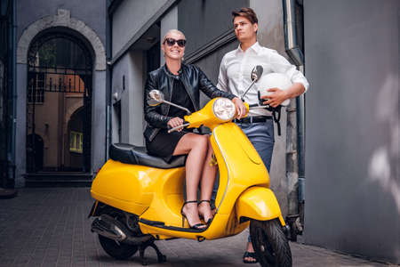 Romantic couple posing with retro Italian scooter in the old narrow street