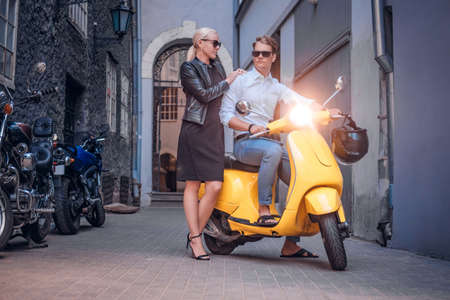 Stylish couple posing with retro Italian scooter in the old narrow street