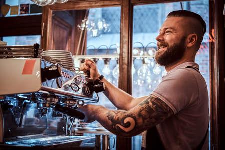 Vrolijke barista met stijlvolle baard en kapsel koffie zetten voor een klant in de coffeeshop