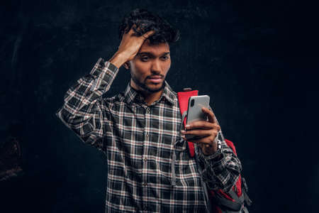 Indian student with a backpack forgot about something very important and with a frustrated look looks at his smartphone. Studio photo against a dark textured wall