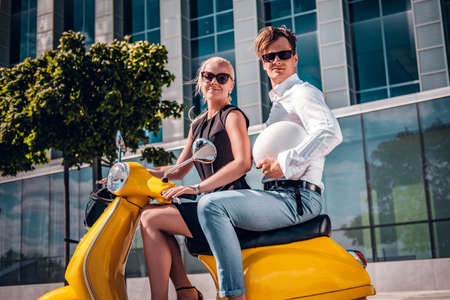 Beautiful romantic couple sitting on a classic Italian scooter on the street of a modern part of a European city Foto de archivo