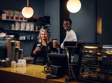 Two happy multiracial baristas holding a coffee while standing behind a counter in a coffee shop or cafe
