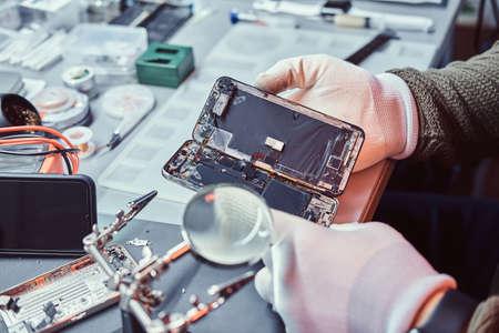 Der Techniker prüft in einer modernen Reparaturwerkstatt sorgfältig die Unversehrtheit der inneren Elemente des Smartphones Standard-Bild