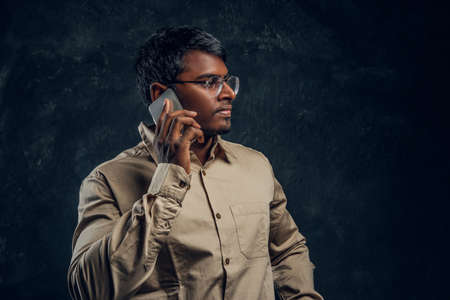 A Hindu doctor looks into the profile, posing and talking on the phone in the studio on a black background Foto de archivo