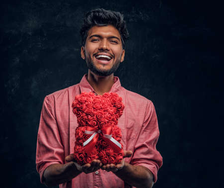 A young Indian guy in a pink shirt holds a beautiful gift, smiling and looking at the camera. Romantic mood, love relationship.