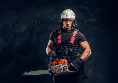 Young logger wearing protective clothing and helmet posing with a chainsaw in a dark studio and looking at a camera