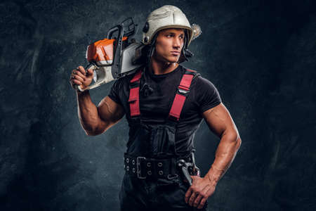 Young lumberjack wearing protective clothes posing with a chainsaw and looks sideways in a dark studio