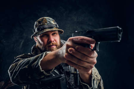 Brutal special forces soldier in the military camouflaged uniform holding a gun and aiming at the enemy. Studio photo against a dark textured wall