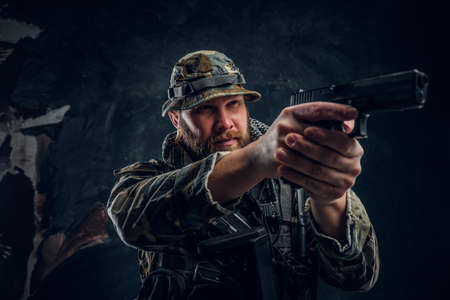 Brutal man in the military camouflaged uniform holding a gun and aiming at the enemy. Studio photo against a dark textured wall