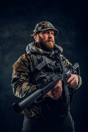 Brutal man in the military camouflaged uniform holding an assault rifle. Studio photo against a dark textured wall