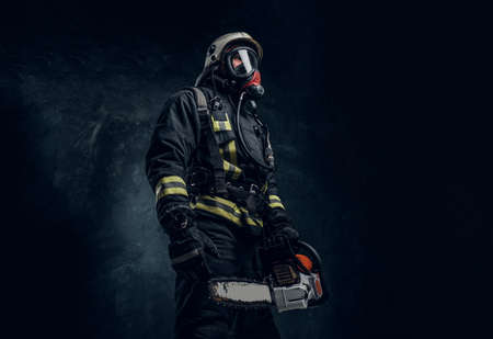 Firefighter in safety helmet and oxygen mask holding a chainsaw. Studio photo against a dark textured wall