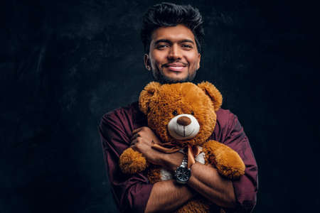 Smiling young Indian man in stylish shirt hugs teddy bear and looking sideways. Studio photo against a dark textured wall