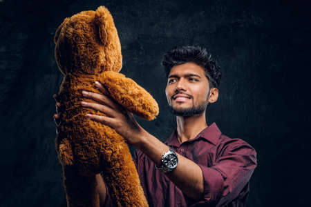 Young Indian guy in stylish shirt looks at his lovely teddy bear while holding it in hands. Studio photo against a dark textured wall Reklamní fotografie