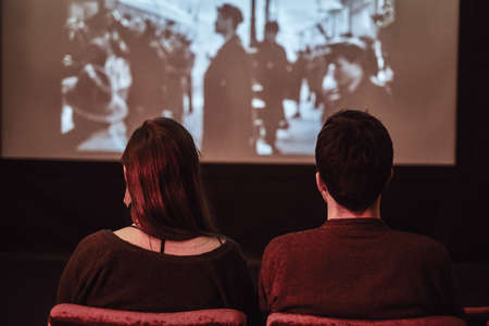 Back view of a young couple on a date watching a retro movie in the cinema