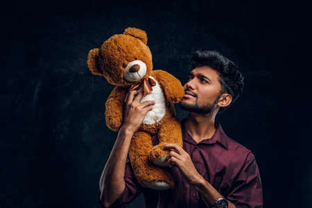 Young Indian guy in stylish shirt looks at his lovely teddy bear while holding it in hands. Studio photo against a dark textured wall
