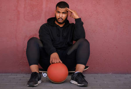 African-American man wearing a black hoodie sitting on a skateboard and holding a basketball while leaning on a wall outside