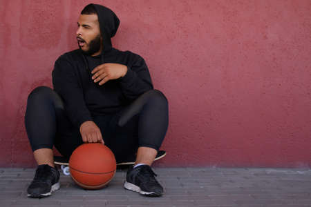 Young African-American man wearing a black hoodie sitting on a skateboard with a basketball, yawning and looking sideways