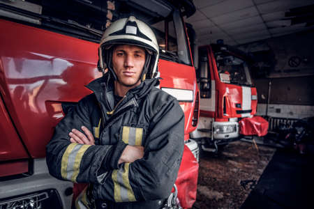 Confident fireman wearing protective uniform standing next to a fire engine in a garage of a fire department, crossed arms and looking at a camera