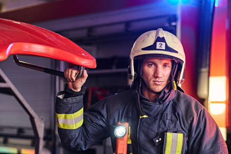 Portrait of a handsome fireman wearing a protective uniform with flashlight included standing in a fire station garage and looking at a camera Stockfoto