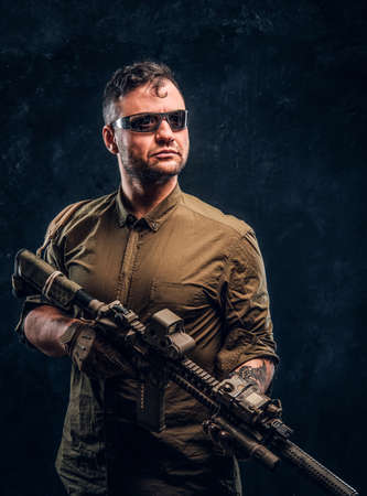 Portrait of a stylish man wearing shirt sunglasses holding assault rifle and looking sideways. Studio photo against a dark textured wall