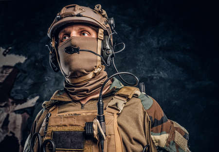 Close-up portrait. Private security service contractor in camouflage helmet with walkie-talkie. Studio photo against a dark textured wall