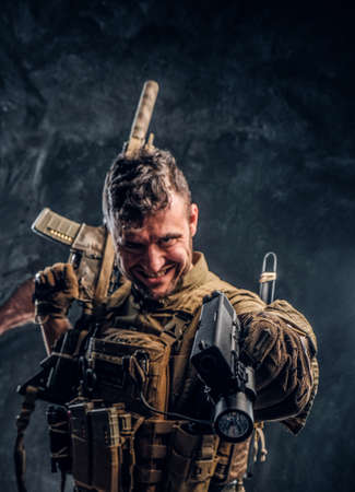 Crazy special forces soldier wearing body armor holding assault rifle and aiming a gun at the camera. Studio photo against a dark textured wall