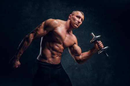 A young guy with a perfect pumped body posing with a dumbbell. Studio photo with dark wall background 写真素材