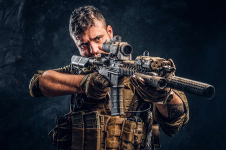 Special forces soldier wearing body armor holding assault rifle and aim at the enemy. Studio photo against a dark textured wall