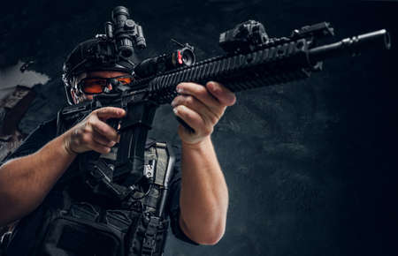 Special forces soldier holding an assault rifle with a laser sight and aims at the target. Studio photo against a dark textured wall Stock Photo