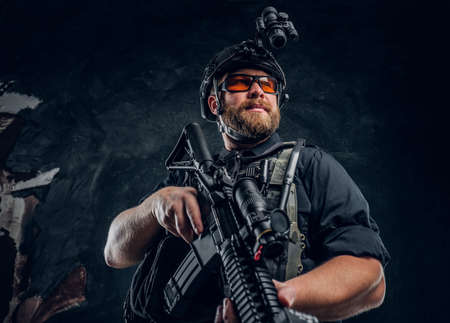 Bearded special forces soldier wearing body armor and helmet with night vision holding an assault rifle. Studio photo against a dark textured wall Imagens