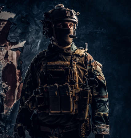 Private security service contractor in camouflage uniform and helmet with walkie-talkie. Studio photo against a dark textured wall Imagens