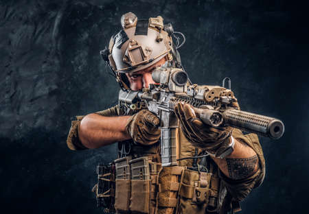Close-up studio photo.Private security service contractor holding an assault rifle with a laser sight and aims at the target.